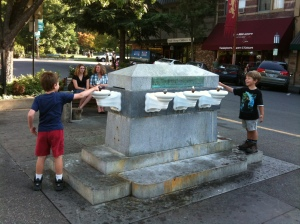 The boys amuse local teens as they splash each other at a fountain in ...